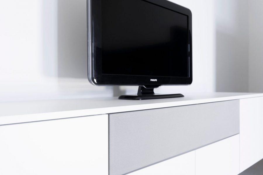 Dit is een voorbeeld van een TV-kast op maat in hoogglans wit met klep en grijs speakerdoek